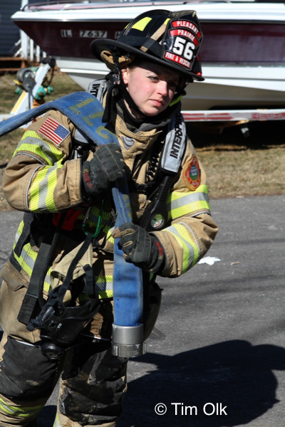 female Firefighter pulling hose