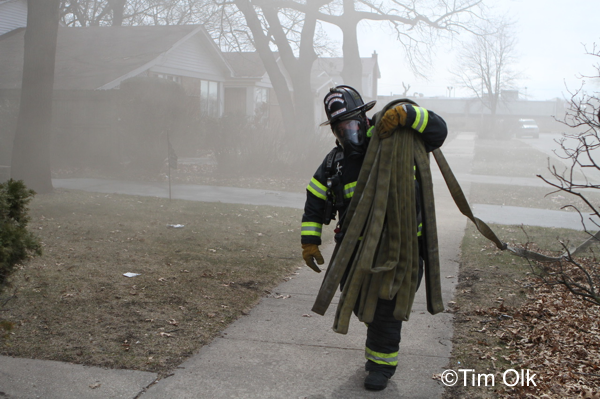 Firefighter carries hose
