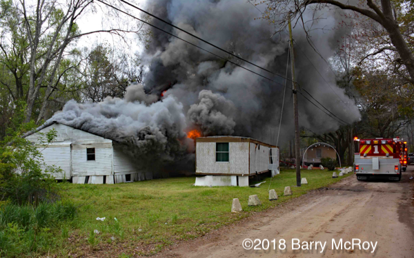 heavy smoke and flames from mobile home on fire