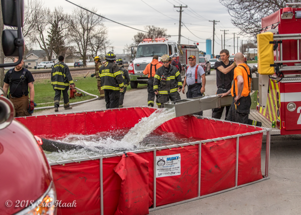 fire department water tender dumps into portable tank