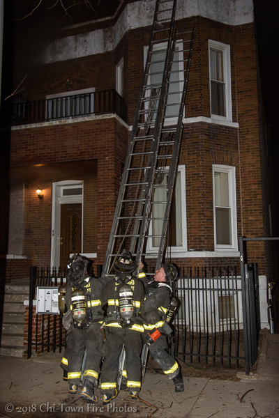 Firefighters raise ladder at fire scene
