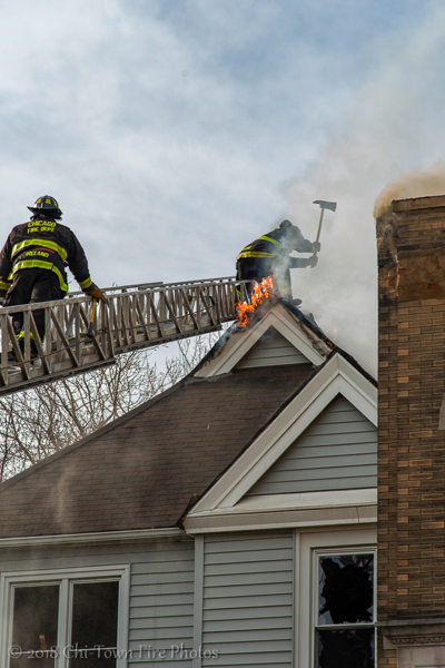 Firefighters vent peak roof with axe