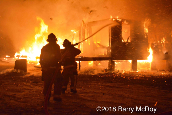 Firefighters silhouetted against massive fire