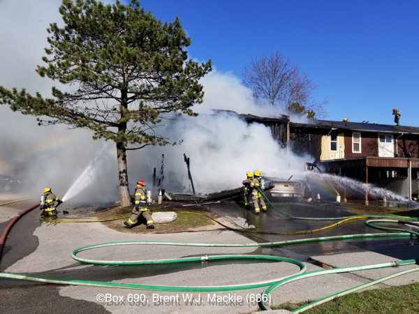 Firefighters operate hose lines at townhouse fire
