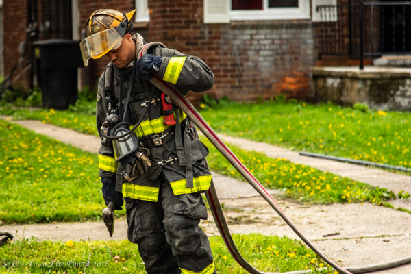 Detroit Firefighter dragging hose