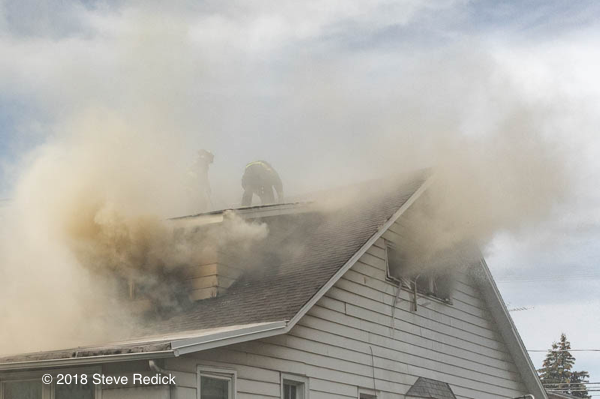 Firefighters vent house fire roof in smoke