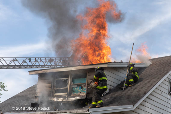 Firefighters vent house fire roof with flames