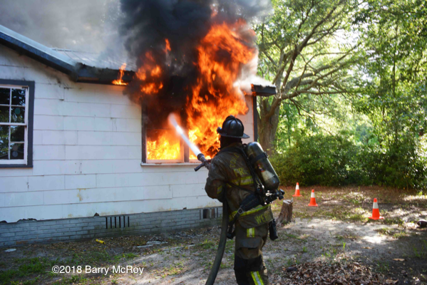 Firefighter with hose battles flames
