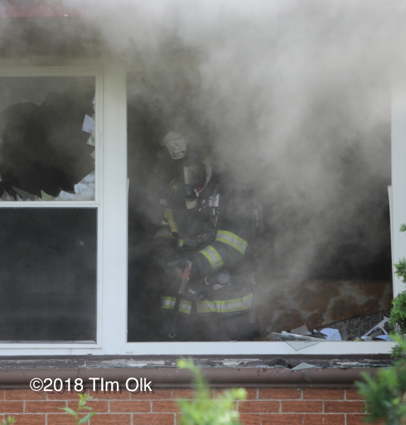 Firefighter with PPE vents window