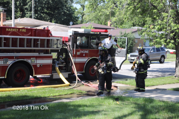 Firefighters pull hose from fire engine