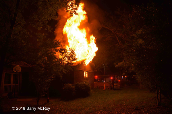 flames engulf house attic at night