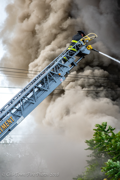 Detroit Firefighter at aerial ladder tip with heavy smoke
