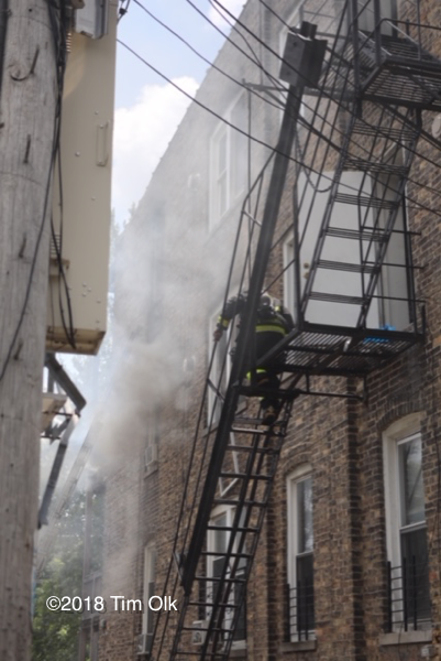 Firefighter on fire escape with smoke