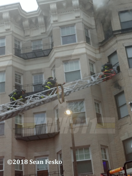 Boston Firefighters on aerial ladder at apartment building fir
