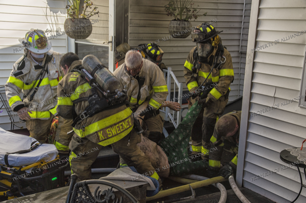 Firefighters crawl from basement after rescuing a victim