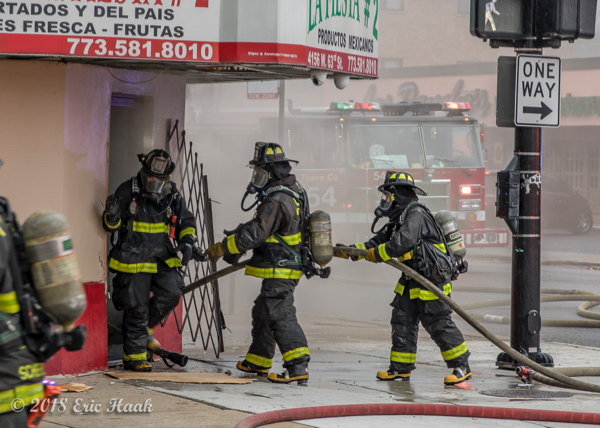 Chicago Firefighters enter grocery store on fire with a hose line