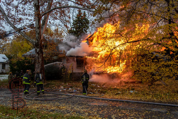 Detroit Firefighters monitor a vacant dwelling engulfed by fire