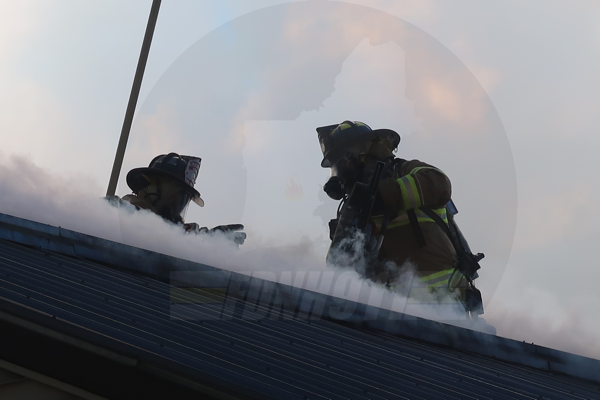 Firefighters on building roof with smoke