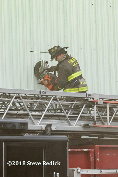 Firefighter vents wall with saw