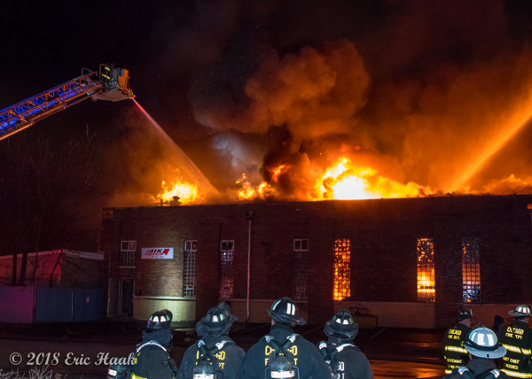 massive flames engulf warehouse at night