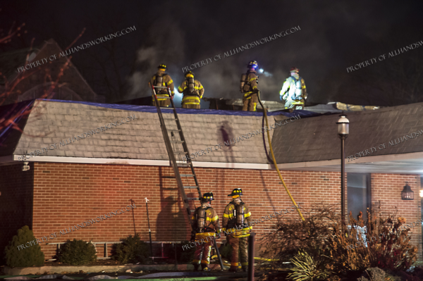 West Haven firefighters extinguish a roof fire at night