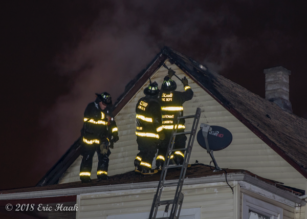 Firefighters on roof during a. house fire
