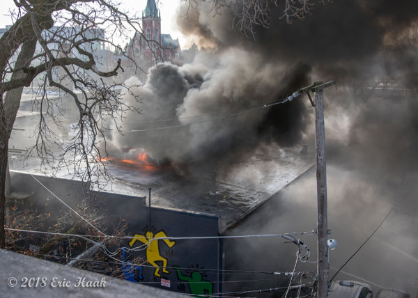 fire burns through a barrel truss roof warehouse