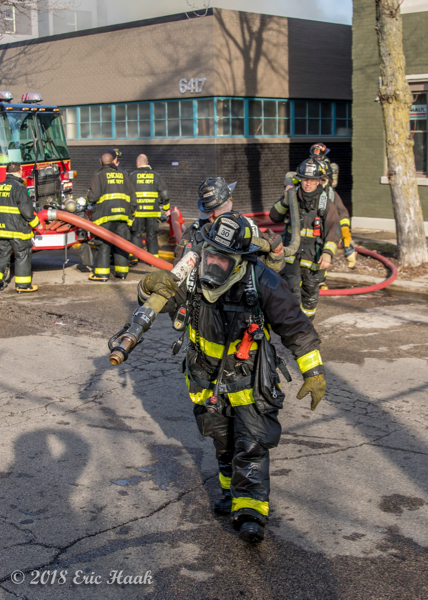 "Firefighters dragging a 2 1/2"" attack line at a fire scene"
