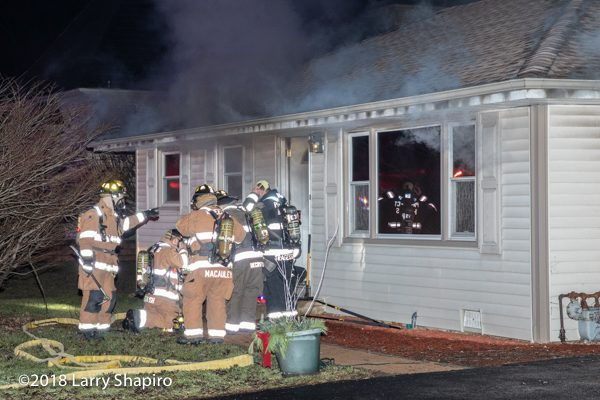 Firefighters prepare to enter a house on fire