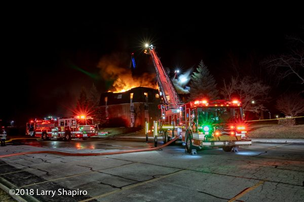 dramatic photo of fire trucks battling a fire at nighr