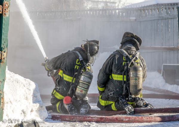 Firefighters with hose line at winter fire
