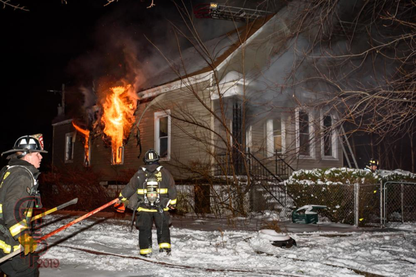 heavy fire blows from house window at night