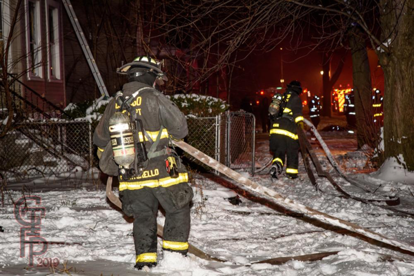 Firefighters pull attack line in the snow