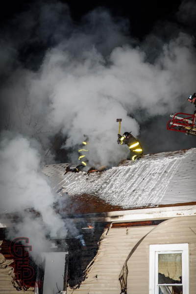 Firefighters vent peak roof with axes in smoke and snow