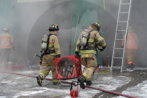 Firefighters carry smoke ejector at fire scene