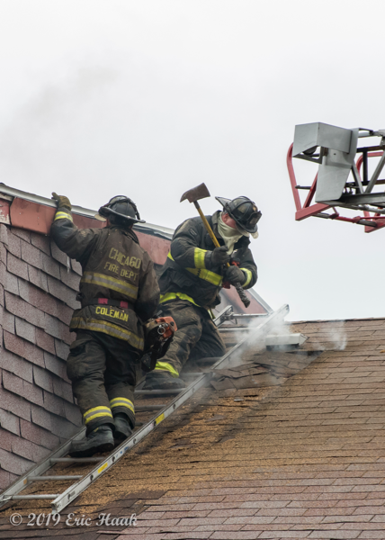 Firefighters vent roof with axe