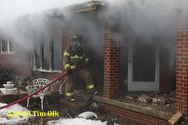 Firefighter holds hose at house fire