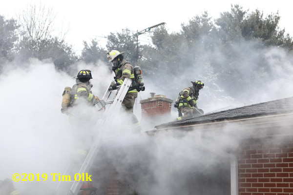 Firefighters on roof of house immersed in smoke
