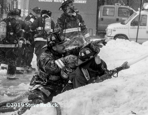 Firefighters with hose line in the snow