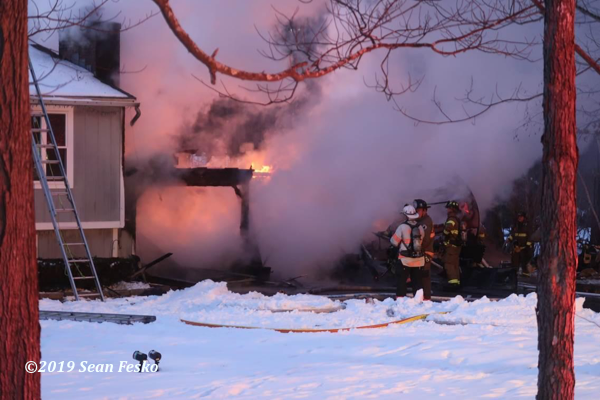 Firefighters at winter house fire scene