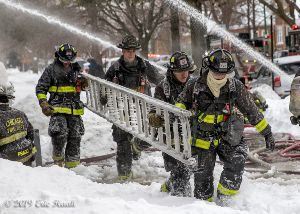 Firefighters carry roof ladder coated with ice at fire scene