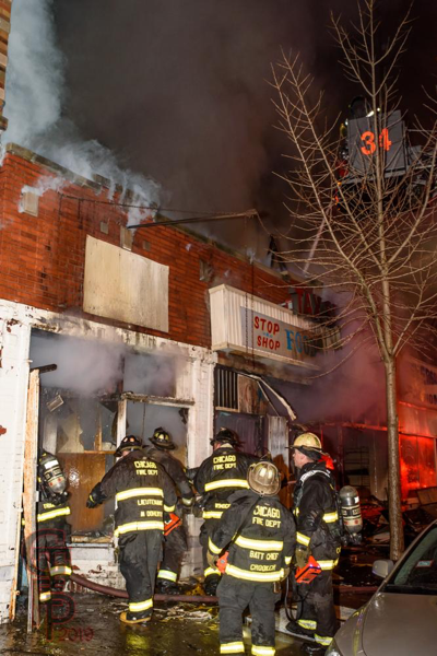 Chicago Firefighters battle a nighttime fire in a storefront