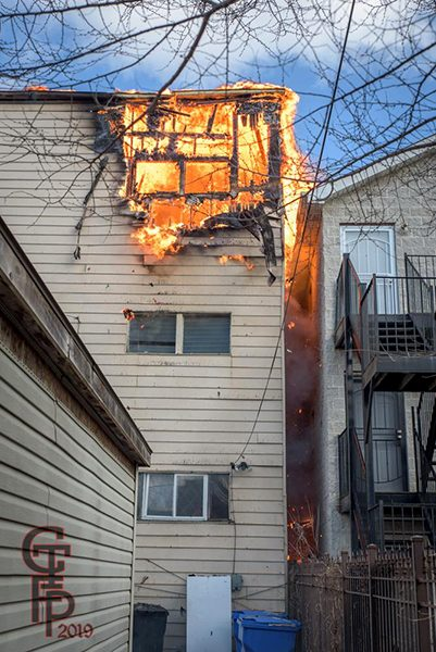 flames burn through third floor of house