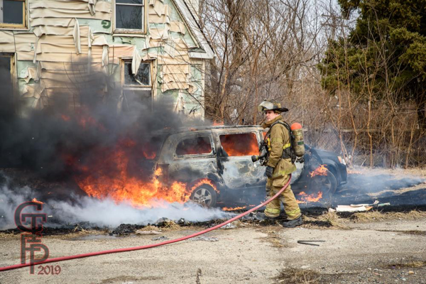 Firefighter prepares to extinguish a minivan destroyed by fire