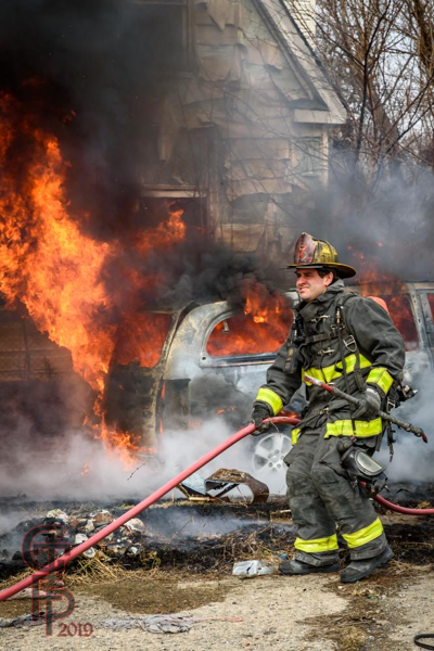 Firefighter prepares to extinguish a minivan engulfed in fire