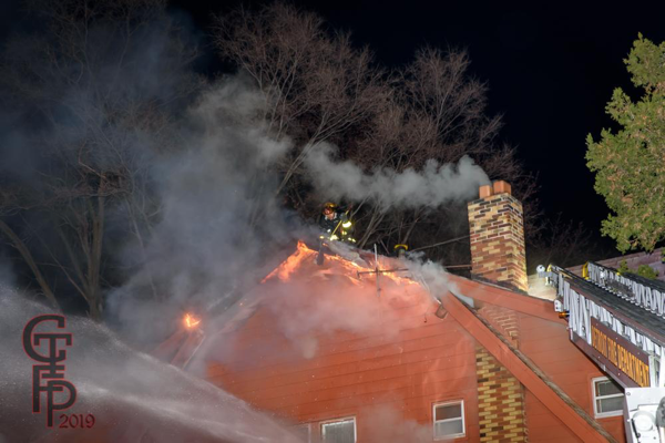 Detroit Firefighter on roof of house fire