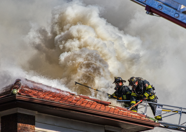Firefighters vent roof from aerial ladder tip with heavy smoke