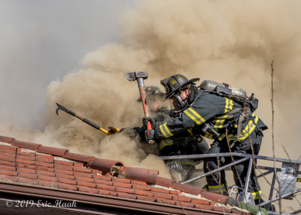 Firefighters ventilate clay tile covered roof