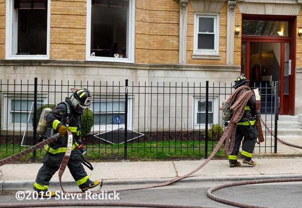 Firefighters pulling hose at a fire