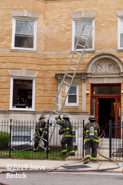 Firefighters raising a ground ladder